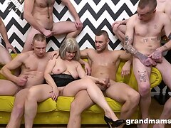 Naked mature is surrounded by younger lads waiting to fuck her hard