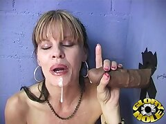Horny MILF drops on the brush knees to swell up a black dick thru a gloryhole